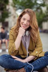 moderne junge frau sitzt auf einer bank mit kopfhörern