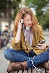 jugendliche sitzt draußen in der stadt und hört musik