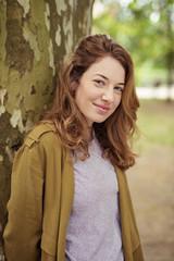 lächelnde junge frau lehnt an einem baum im park
