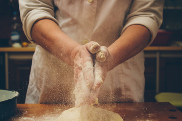 Chef clapping hands full of flour over fresh dough