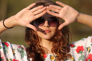Hippie girl in sunglasses covers her face from the sun hand