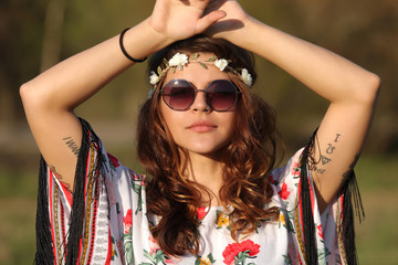 Young woman in hippie style holding hands on head