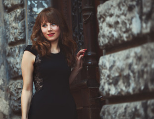 portrait of a cute woman in hot dress leaning on the wall