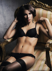 Beautiful and sexy girl in underwear sitting in a vintage armchair
