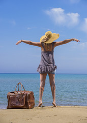 Woman with leather travel bag on the beach