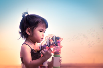 Vintage color filltered of cute little girl having fun blowing b