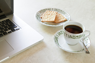 Coffee cup and cracker with laptop on marble table