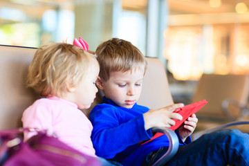 kids looking at touch pad while travel in the airport