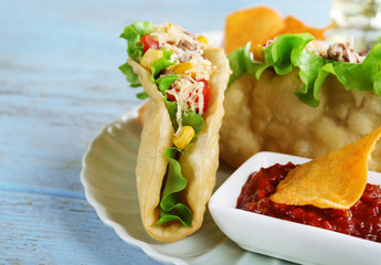 Tasty taco with tomato dip on plate and vegetables