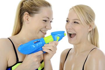 Frauen in Bikini albern mit Wasserpistole