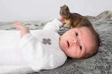 Very cute one -month old baby in a grey blanket