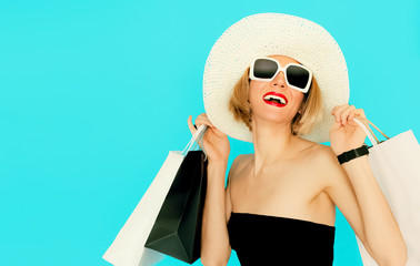 Happy shopping woman holding bags on blue background