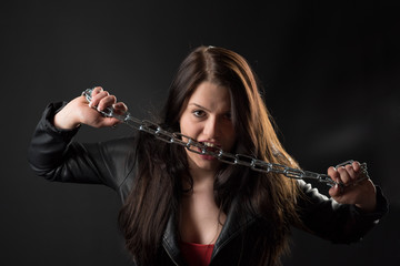 Frau in Lederjacke beißt in eine Eisenkette