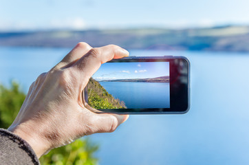 Tourist Taking a Picture of Loch Ness with a Smartphone
