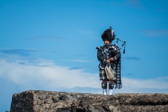 Traditional bagpiper in the scottish highlands near Pennan