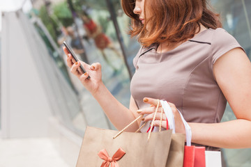 Happy fashion woman with bag using mobile phone, shopping center