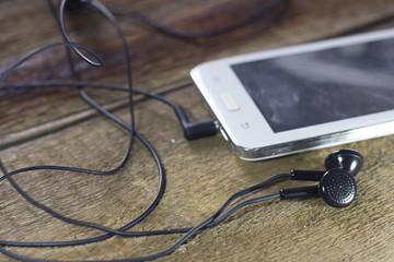 White smart phone with earphones