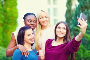 group of multiracial girls taking selfie on smartphone