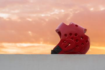 Red Taekwondo head guard with on sunset background.