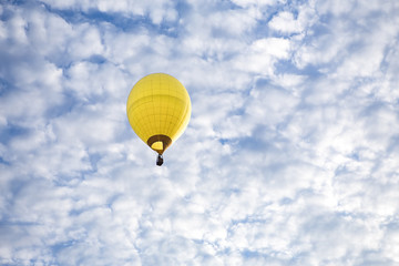 A Yellow Hot Air Balloon floats high in the sky.