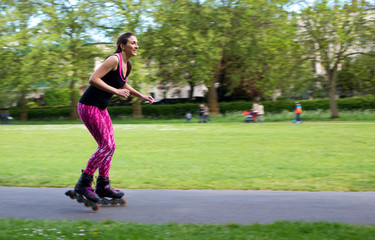 panning shot of a young woman rollerblading in the park