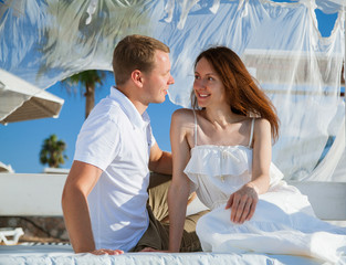 Happy young couple  sitting under a beautiful white baldachin