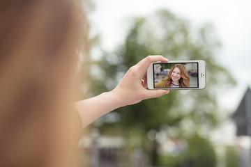 frau macht ein selbstportrait mit ihrem mobiltelefon