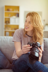 frau sitzt auf dem sofa und hält ihre kamera in der hand