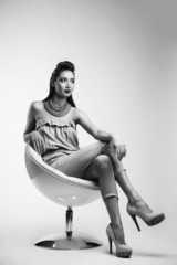 Studio shoot of beauty woman posing on the chair. Black and whit