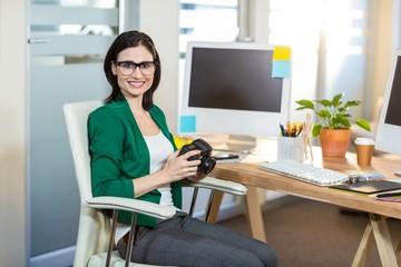 Smiling brunette holding digital camera