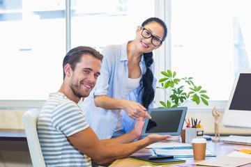 Smiling partners working together on tablet