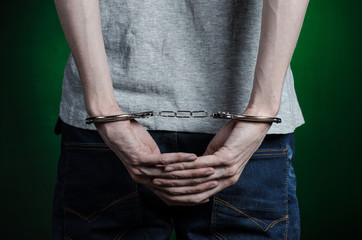 man with handcuffs on his hands in blue jeans on a dark green