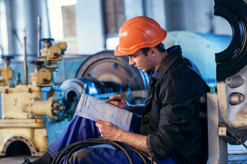 Worker on industry studying manual instructions repair turbine.