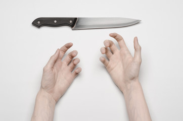 A man's hand reaching for a knife isolated on a gray background