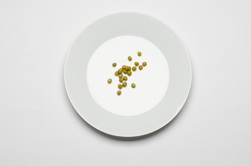 green peas lying on a white plate on a white table top view
