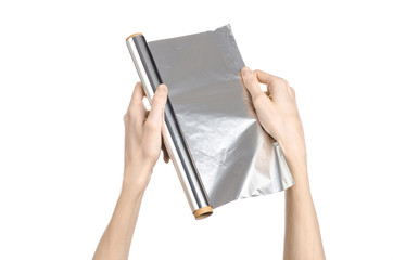 human hand holding a roll of foil on a white background