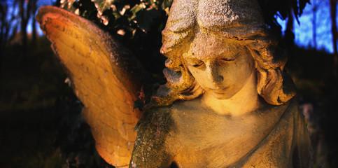 sculpture of an angel with dark background