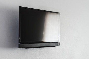 Black LCD or LED tv screen hanging on wall