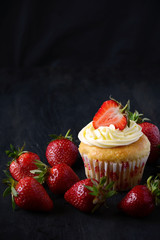Capcakes with strawberries on dark background