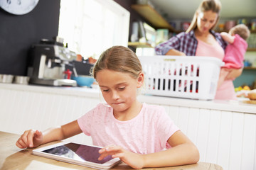 Girl Using Digital Tablet As Mother Sorts Laundry