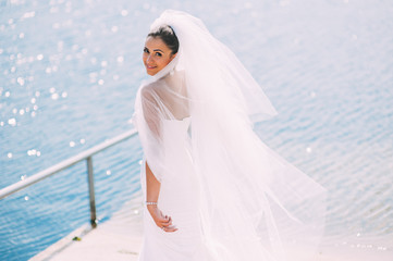 Bride posing on the pier at the lake