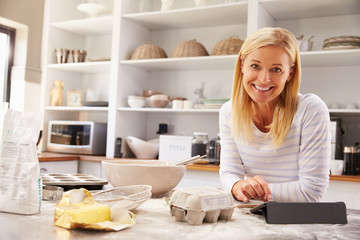 Woman baking at home following recipe on a tablet