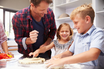 Father making pizza with kids