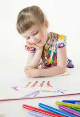Pretty little girl lying on the floor and looking on her drawing