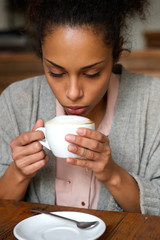 Young african american woman drinking cup of coffee