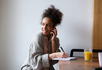 Female student working at home and talking on mobile phone