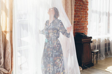 girl opening curtains in a bedroom