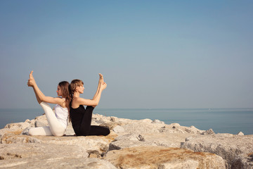 Beautiful stretch  girls practicing yoga fitness on the beach on the rocks, Krounchasana yoga posture