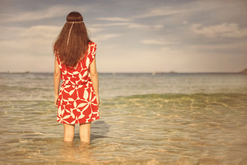Young pretty woman in red dress standing and thinking on the sea