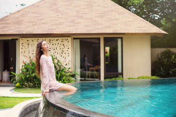 Beautiful young woman enjoying sun sitting near swimming pool at luxury villa